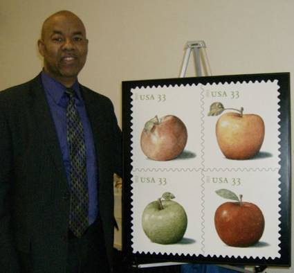 Seattle District Manager Yul Melonson showcases the new Apples stamp issue.