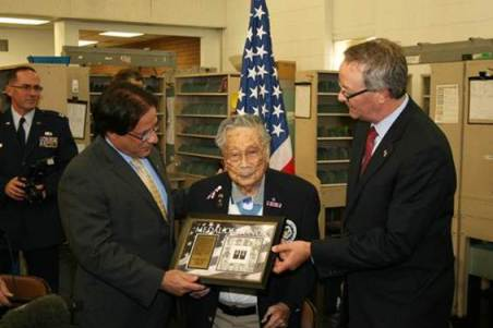 Western Area AVP Drew Aliperto and Denver Postmaster Mark Talbott present retired employee and Medal of Honor recipient George Sakato a framed art piece of the new Medal of Honor Forever stamp.