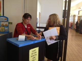 Retail Associate Roberta Castaneda helps a customer with her mailing.