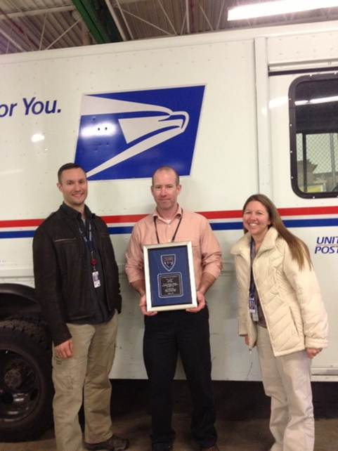 Fairbanks, AK, Postmaster Hal Barber, center, was presented a plaque and commendation by Special Agents from the OIG, Georg Brendel, left, and Sara Harlan-Upp.