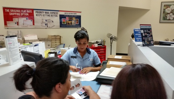 Retail Associate Soledad Robinson works with a customer on her passport.