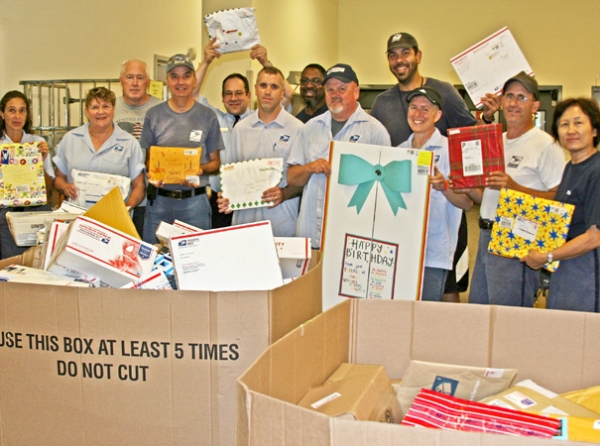 Foxboro, MA, plant employees stand behind two containers full of packages and letters for Danny Nickerson.