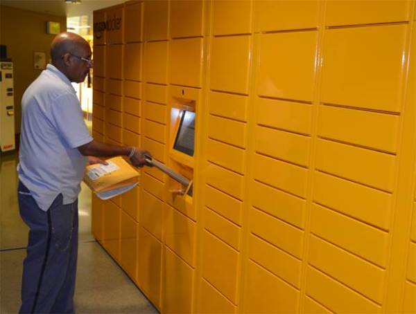 Seattle Letter Carrier Berhane Solomon scans a parcel destined for an Amazon.com locker.
