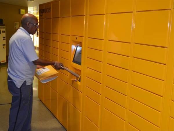 Seattle Letter Carrier Berhane Solomon scans a parcel destined for an Amazon.com locker.