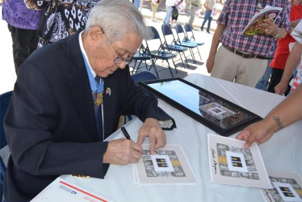 Medal of Honor recipient Hiroshi Miyamura signs autographs for event attendees.
