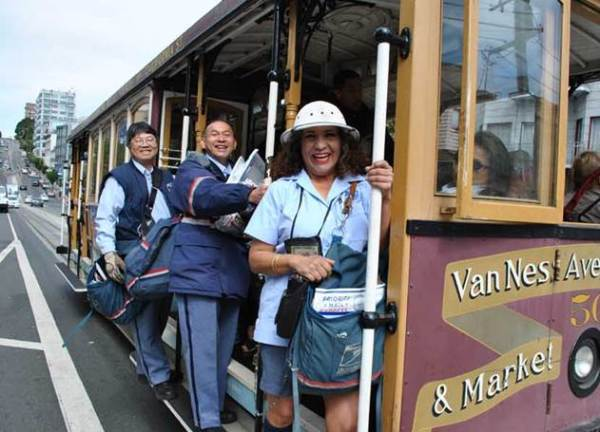 San Francisco City Carriers Lau Ming, Daryl Ha and Alma Silva-Orden pose aboard the famous cable cars they use to travel to and from their delivery routes.