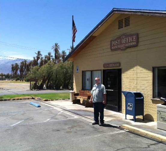 Death Valley Postmaster William VanBokkelen surveys the hot summer landscape outside his Post Office.