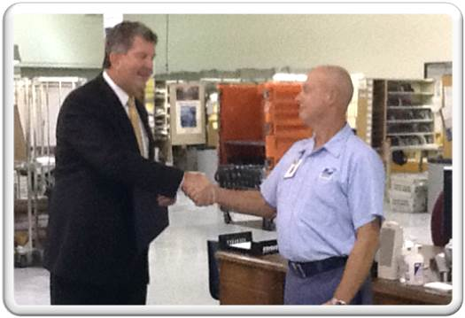 PMG Donahoe congratulates City Carrier Larry Allen on his 45 years of service.
