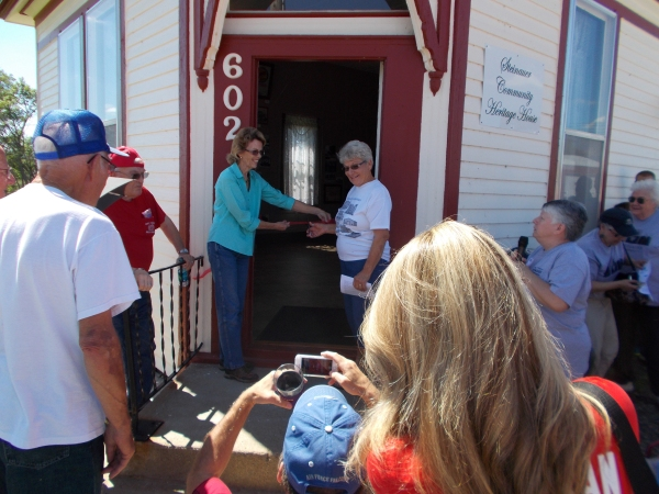 Joann Lutcavich and Erma Gyhra cutting the ribbon for the dedication of the Steinauer Community Heritage House.