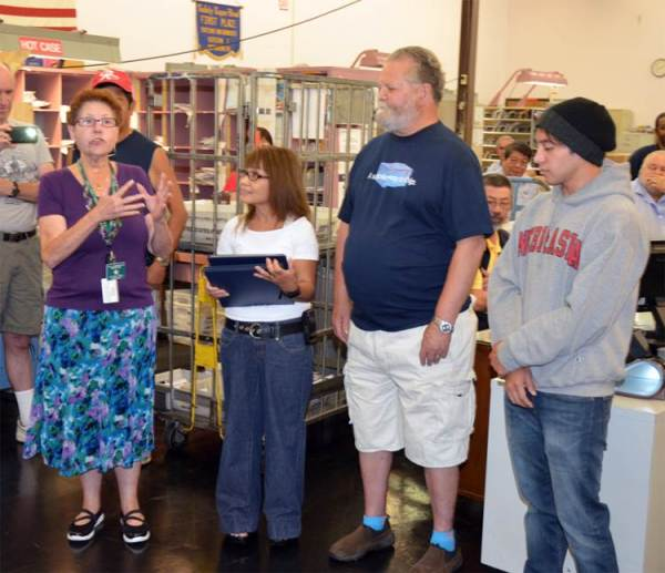 NALC Branch 79 President JoAnn Pyle congratulates Jerry Jonason, second from the right, on his retirement after 57 years as a Letter Carrier in Seattle. To his right is his wife and to his left is their son.
