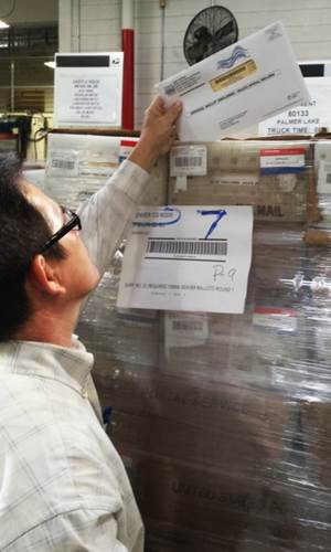 Denver P&DC Dock Supervisor Dzung Nguyen verifies a tray that holds just a few of the 3.5 million ballots mailed in Colorado's first all-mail ballot election.