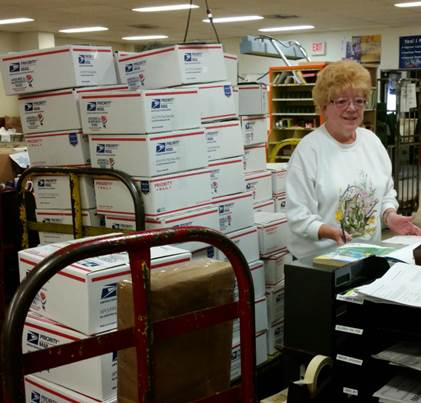 Pat Greer with some of the Priority Mail care packages destined for troops overseas.