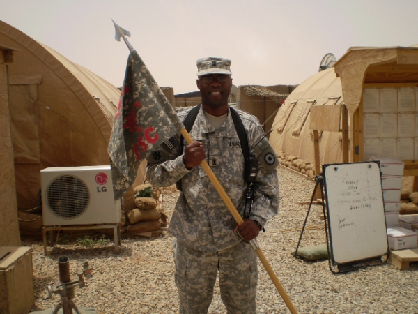 U.S. Army First Sergeant Richard Flowers holds the guidon for 1161 Forward Support Company.