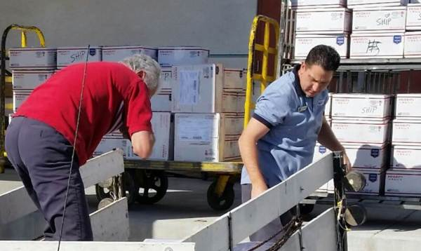 Laughlin, NV, Retail Associate Al Sarabia helps  a member of St. John's Catholic Church load Priority Mail packages onto a GPMC.