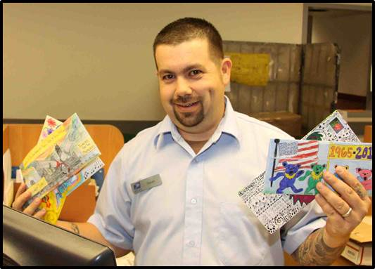 Downtown Denver Station Retail Associate Jason Meding holds some of the more colorful pieces of mail that were mailed from Grateful Dead fans looking to score tickets.