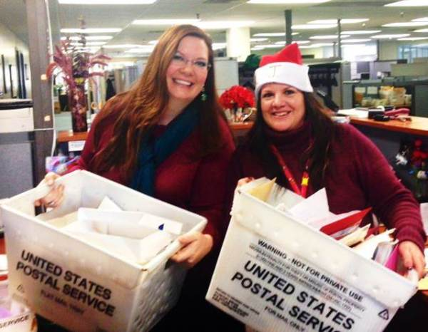 Acting Consumer and Industry Contact Manager Michelle Cotton along with Operation Santa Coordinator Kathy Jaramillo showcase some of the many letters received from children.