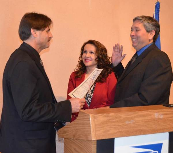 Arizona District Manager John DiPeri swears in Albuquerque Postmaster Severo Garza. Severo's wife, Sylvia Guerra-Garza, looks on as her husband accepts the responsibility of his new position.