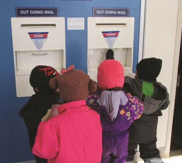 Young mail enthusiasts drop letters in the outgoing mail slot at the Leadville, CO, Post Office.