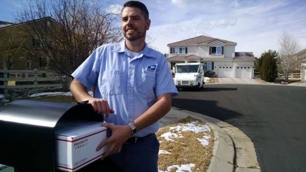 Letter Carrier JD Kohl demonstrates the capacity of the new mailboxes.