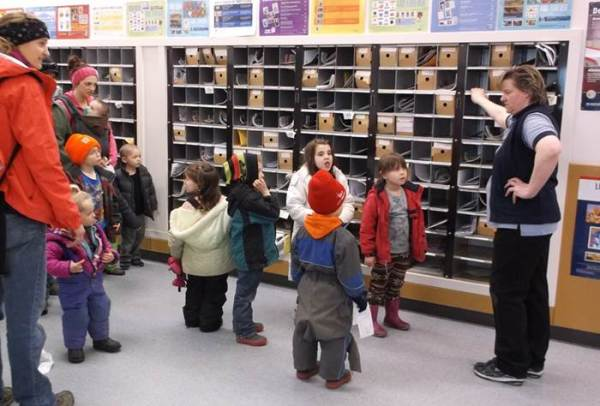 Anchor Point, AK, Retail Associate Melody Martin takes kids on a tour of the post office for National Card and Letter Writing Month.