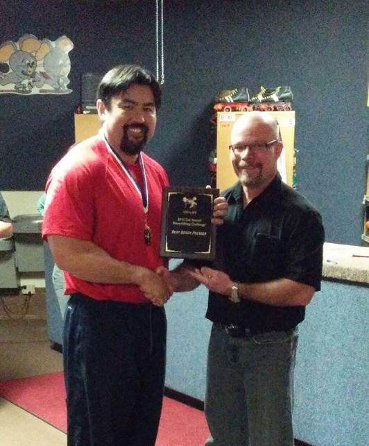 Postmaster Mike Brownfield (left) received a plaque for his bench press prowess.