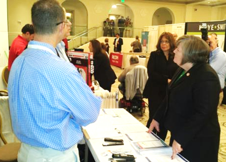 PMG Megan Brennan visits business mailers' booths at the PCC event.