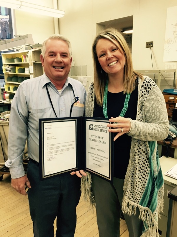 Glendive, MT, City Carrier Perry Nentwig receives his 30-year service award from Postmaster Brandi Lien.