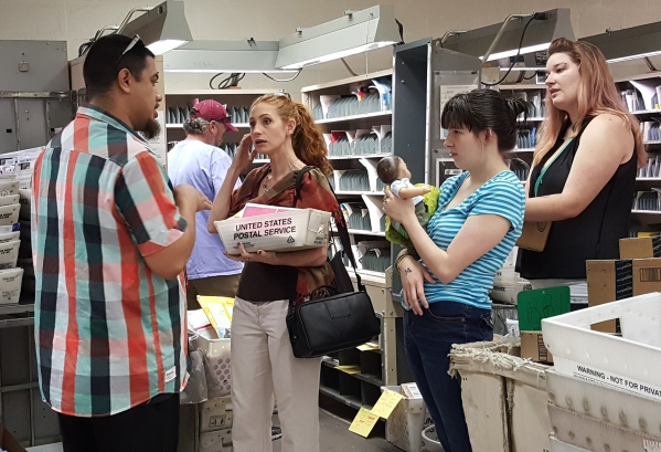Customer Services Supervisor Leon Hernandez shows Andra, Sarah, and Sarah's sister-in-law how the mail is sorted each day.