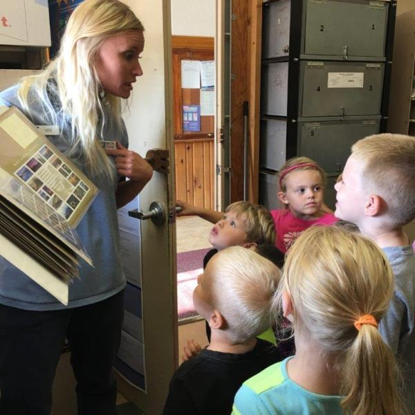 Little River, KS, Retail Associate Leslie Schneider providing a tour of her office to local children.