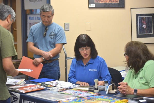 Two customers peruse the many philatelic collectibles with Albuquerque, NM, P&DC General Clerk Lori Aldrich and Main Office Retail Associate Cecilia Padilla.